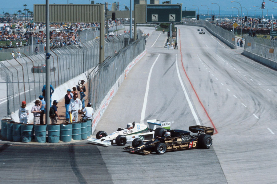 Alan Jones dives up the inside of Mario Andretti