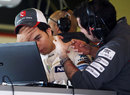 Sergio Perez talks to his engineer after Sauber discovered a problem with his car
