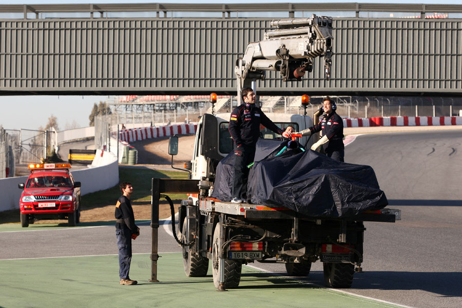 The stricken Toro Rosso is recovered on the back of a truck