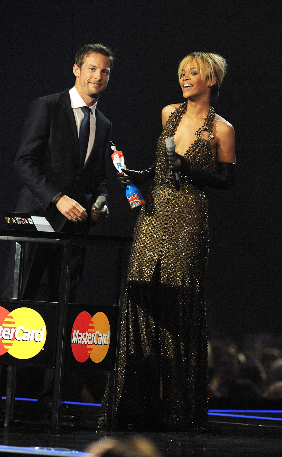 Jenson Button presents Rihanna with an award at the Brit Awards