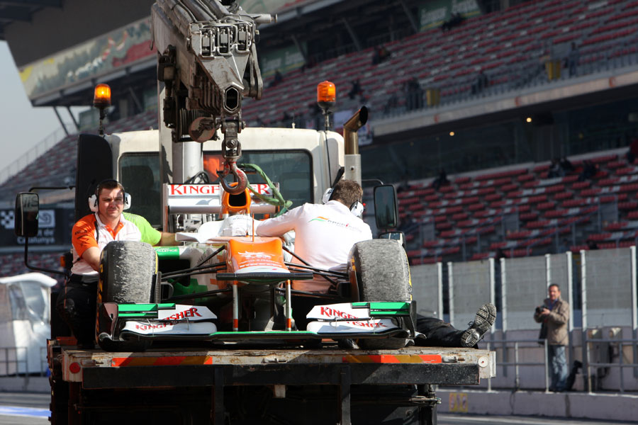 Paul di Resta's Force India is returned to the pits after his off at turn 9