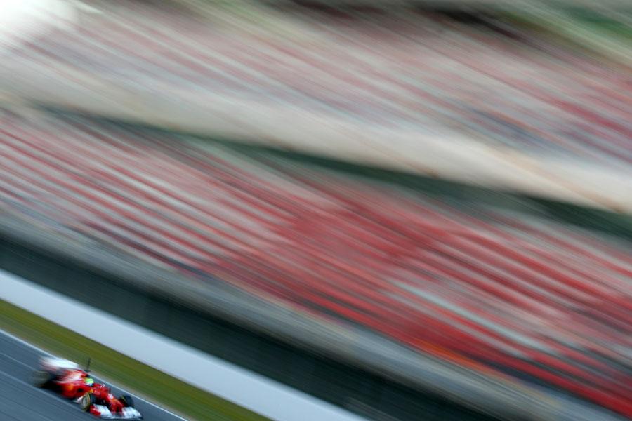 Felipe Massa speeds past the main grandstand at the Circuit de Catalunya