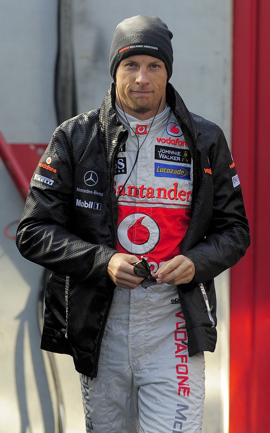 Jenson Button listens to music and tries to keep warm in the paddock