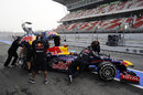 Sebastian Vettel is wheeled back in to the garage as Red Bull mechanics cover the car with umbrellas