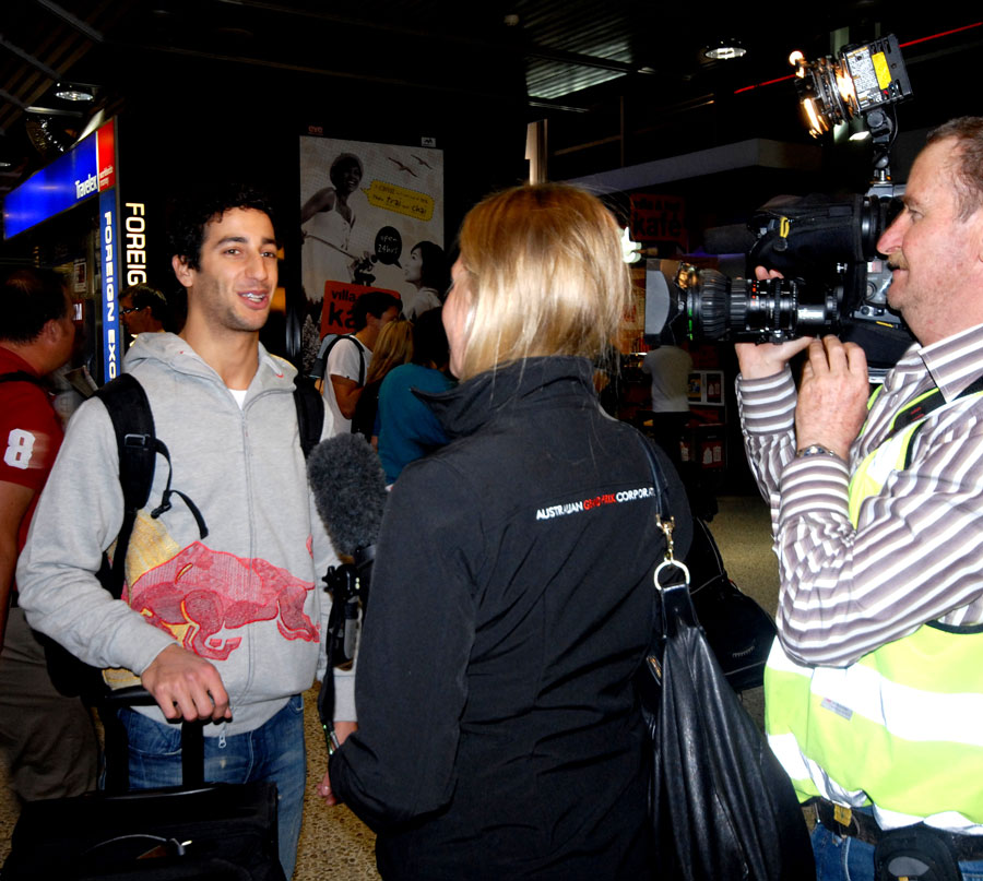 Daniel Ricciardo gets interviewed on his arrival at the airport