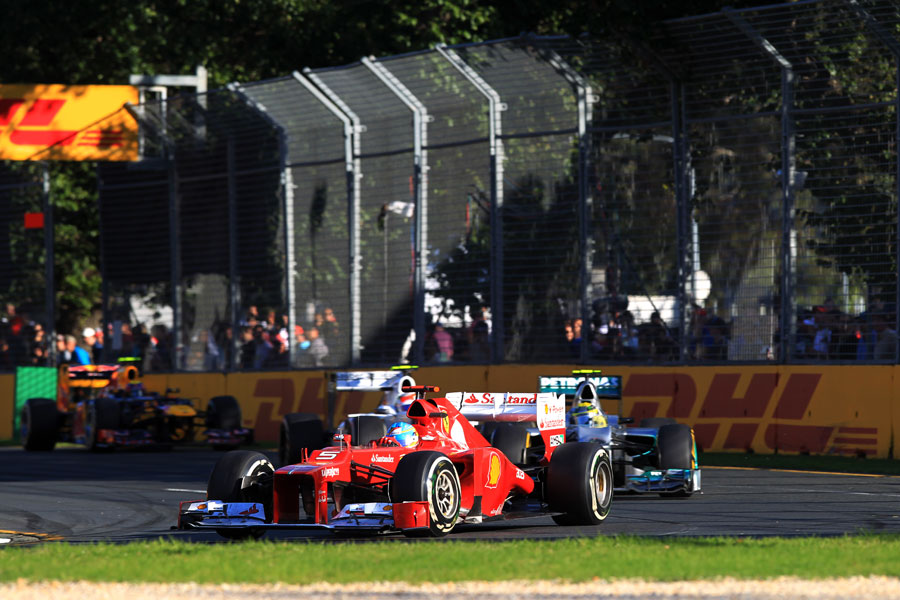 Fernando Alonso holds off Nico Rosberg in to turn three