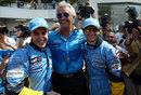 Flavio Briatore celebrates with Fernando Alonso and Jarno Trulli after locking out the front row