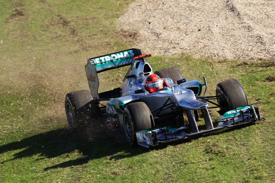 Michael Schumacher runs across the grass before retiring