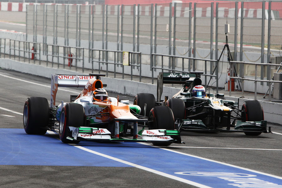 Nico Hulkenberg passes Vitaly Petrov in the pit lane