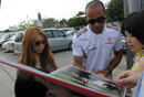 Lewis Hamilton signs a picture of himself driving in GP2 for fans in the paddock