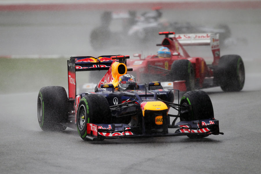 Sebastian Vettel comes under pressure from Fernando Alonso as the rain increases