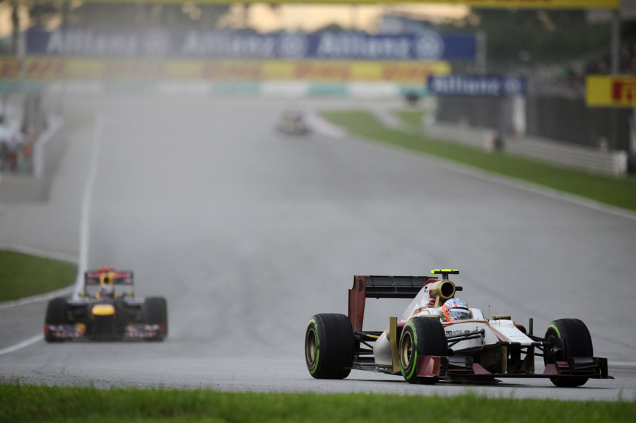 Narain Karthikeyan enters the final corner with Sebastian Vettel closing in
