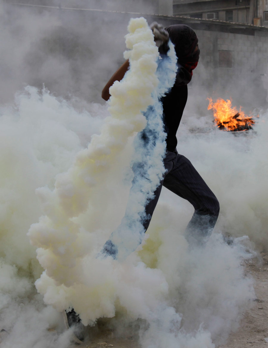 A Bahraini anti-government protester throws a tear gas canister fired by riot police back toward them