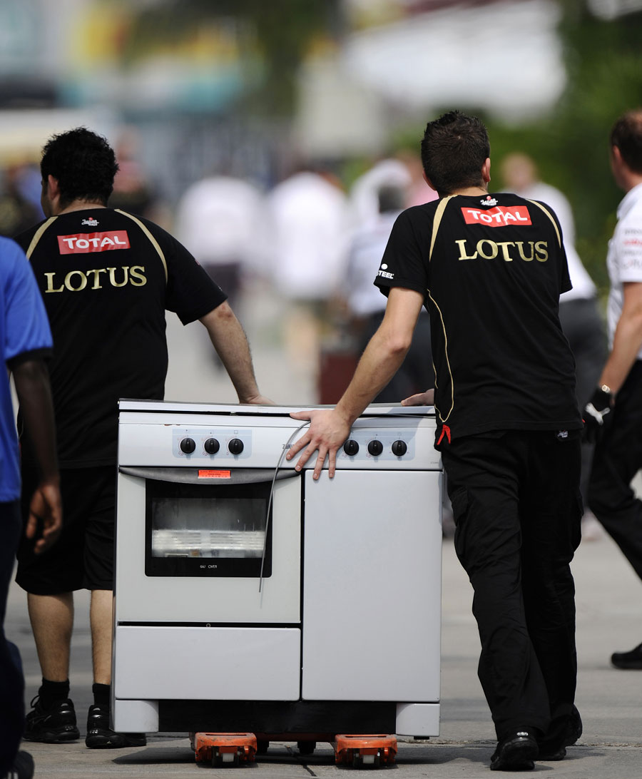 Lotus team members move a cooker after a fire in its hospitality unit