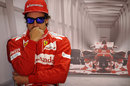 Fernando Alonso watches on nervously from the back of the Ferrari garage