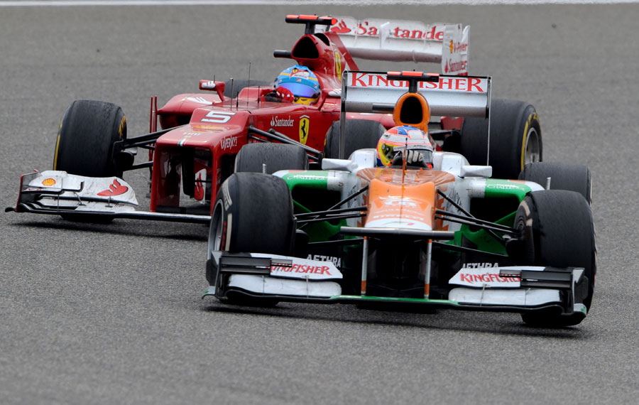 Paul di Resta holds of Fernando Alonso