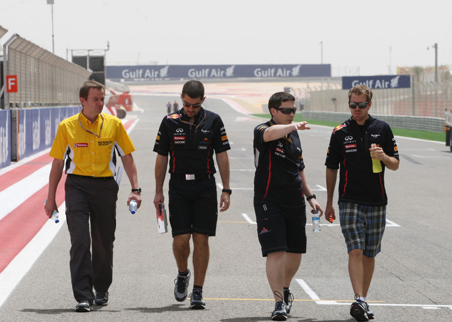 Sebastian Vettel walks the track with his engineers