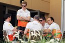 Nico Hulkenberg and Paul di Resta chat with team members in the paddock