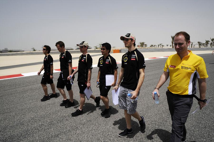 Romain Grosjean walks the track with his Lotus team