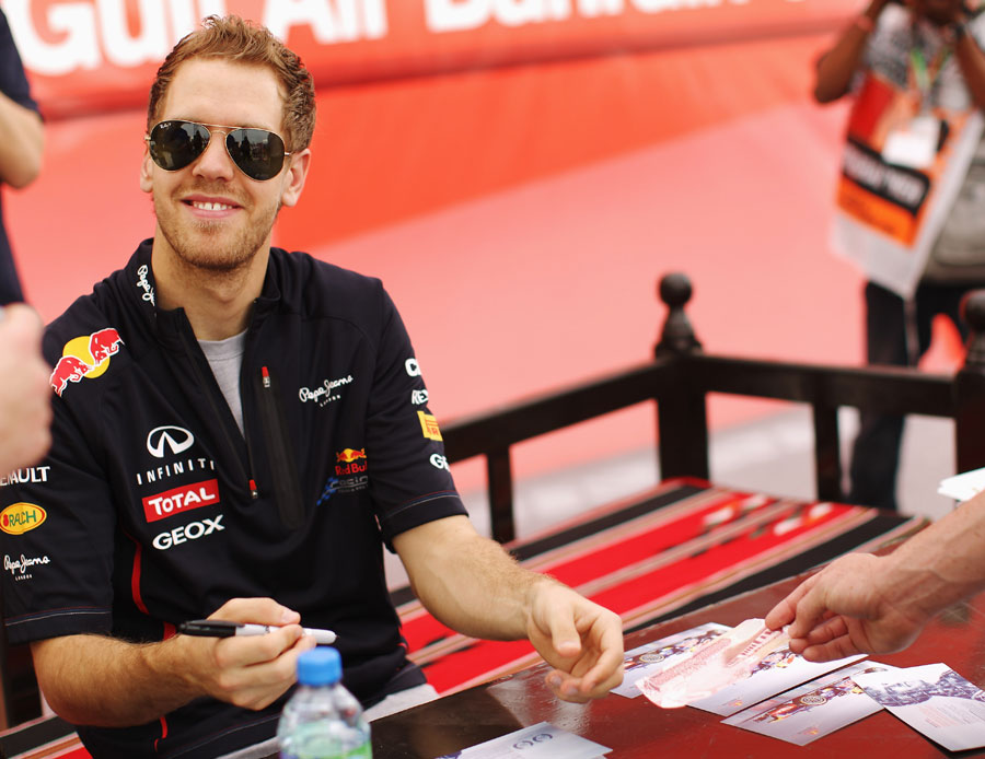 Sebastian Vettel signs autographs on race day morning