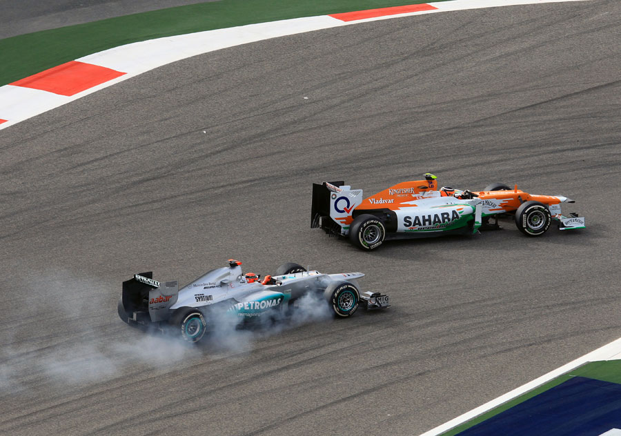 Michael Schumacher locks a wheel while attempting to pass Nico Hulkenberg