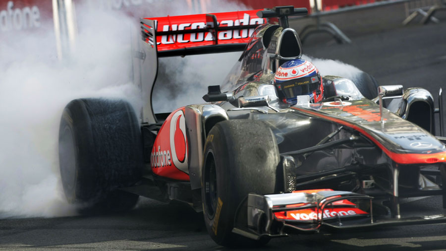 Jenson Button burns rubber during a demonstration run in Budapest