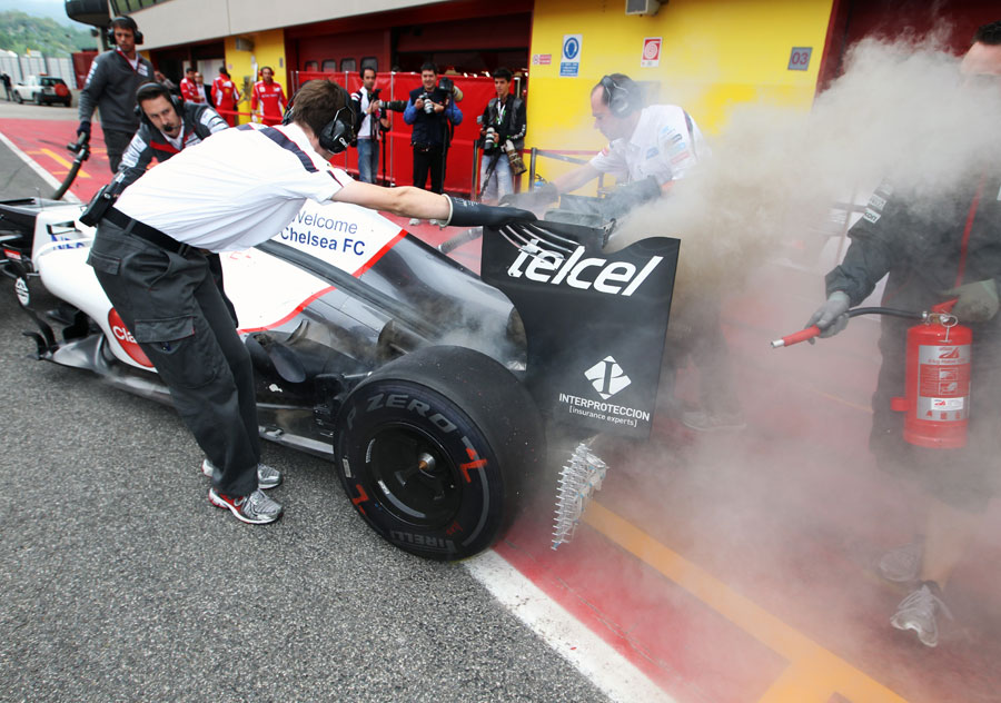 Sauber mechanics deal with a flash fire in the pit lane