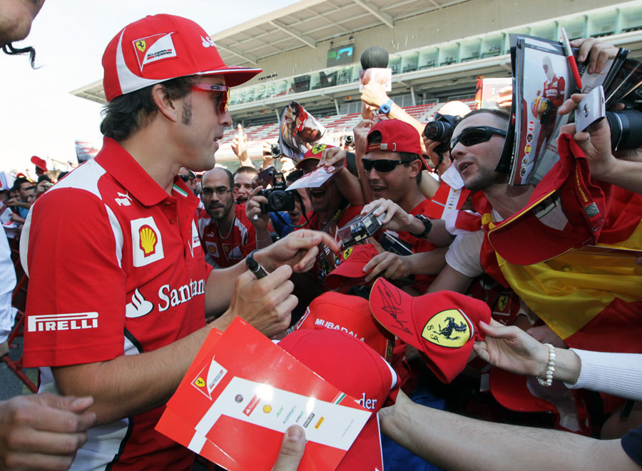 Fernando Alonso signs autographs for fans in the pit lane