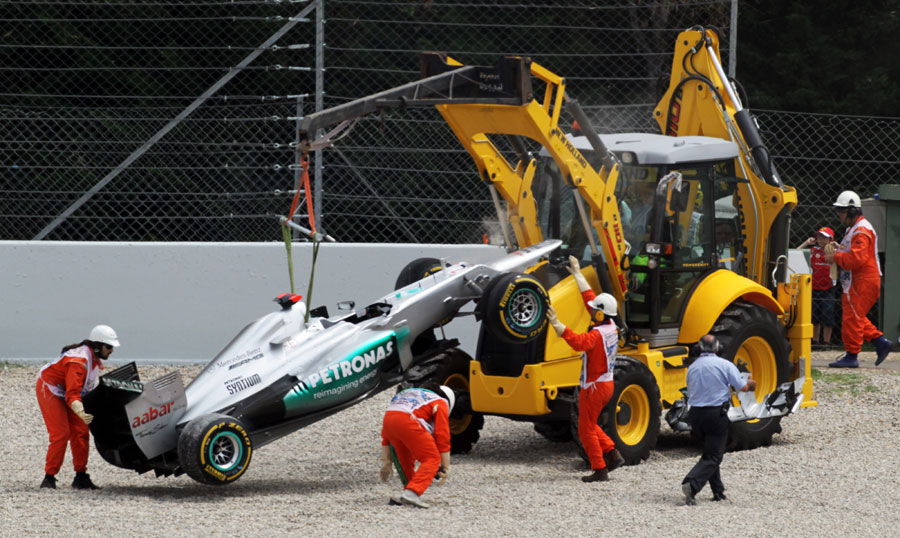 Michael Schumacher's Mercedes is hauled away after his collision
