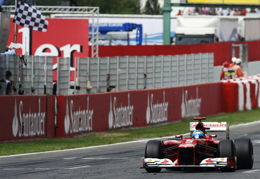 Fernando Alonso crosses the line to take second