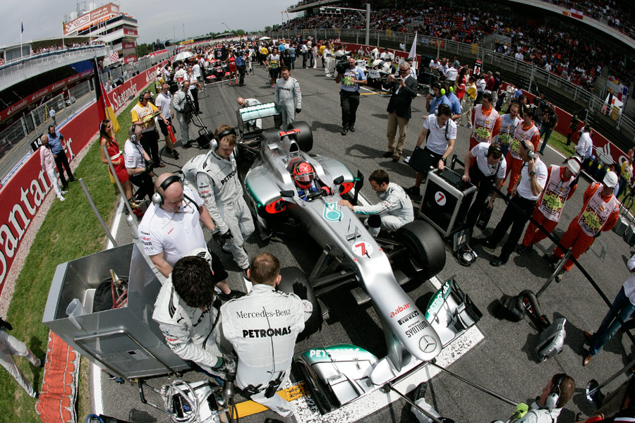 Michael Schumacher prepares to race as his pit crew make last-minute adjustments
