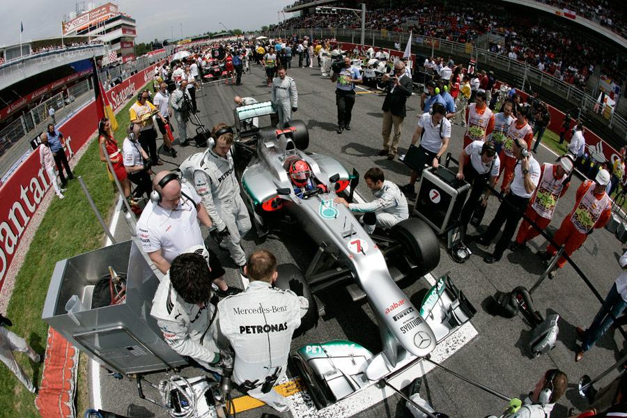 Michael Schumacher prepares to race as his pit crew make last-minute adjustments