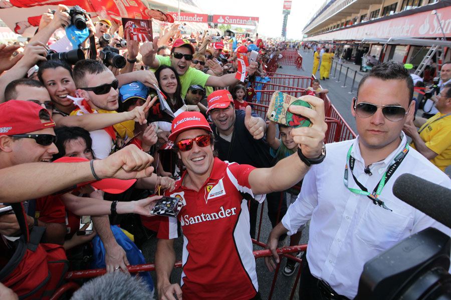 Fernando Alonso takes his photograph with fans in the pit lane