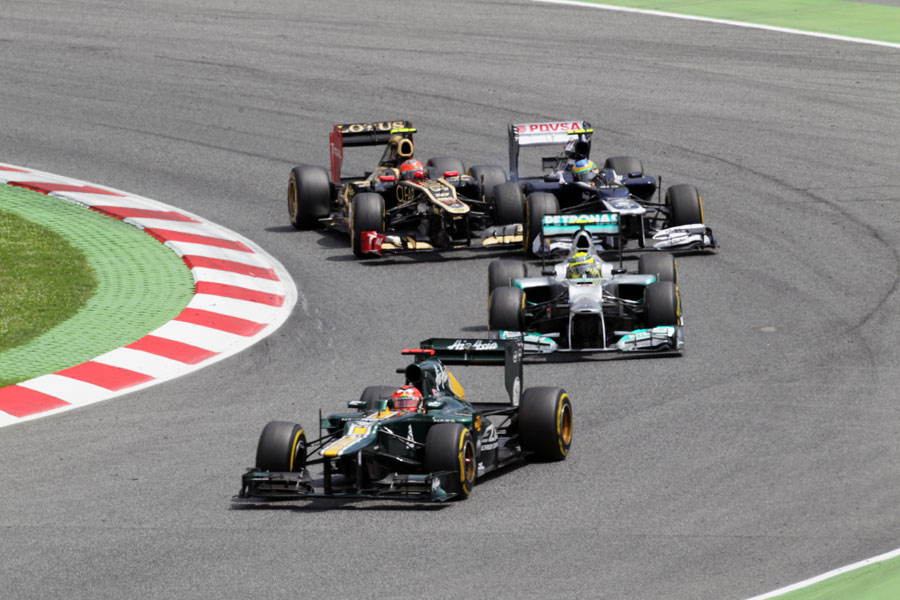 Heikki Kovalainen leads Nico Rosberg through turn one as Romain Grosjean and Bruno Senna battle behind
