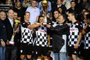 Michael Schumacher, Felipe Massa and Vitaly Petrov celebrate victory in the charity football match alongside Prince Albert of Monaco