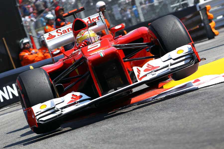 Fernando Alonso launches his Ferrari over the kerbs