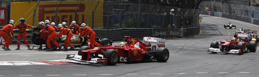The Ferraris of Fernando Alonso and Felipe Massa pass the stricken Romain Grosjean