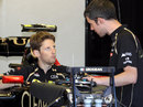Romain Grosjean talks to his mechanic in the Lotus garage
