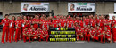 The Ferrari team pose with a banner reading