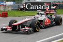 Jenson Button returns to the pit lane