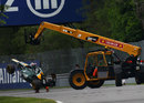 Heikki Kovalainen's Caterham gets lifted away by marshals