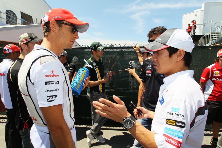 Jenson Button and Kamui Kobayashi chat before the driver parade