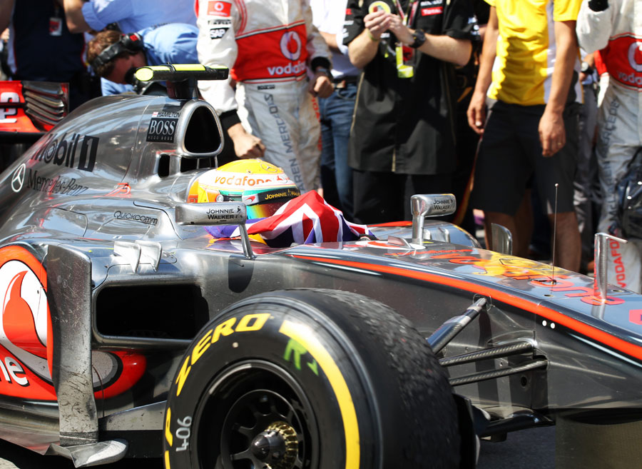 Lewis Hamilton celebrates his victory as he returns to the pits