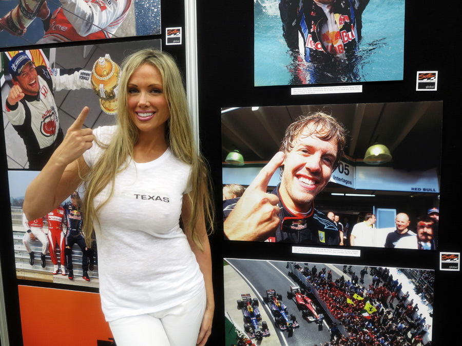 A glamour model poses in front of photos at the Formula One Expo in Austin