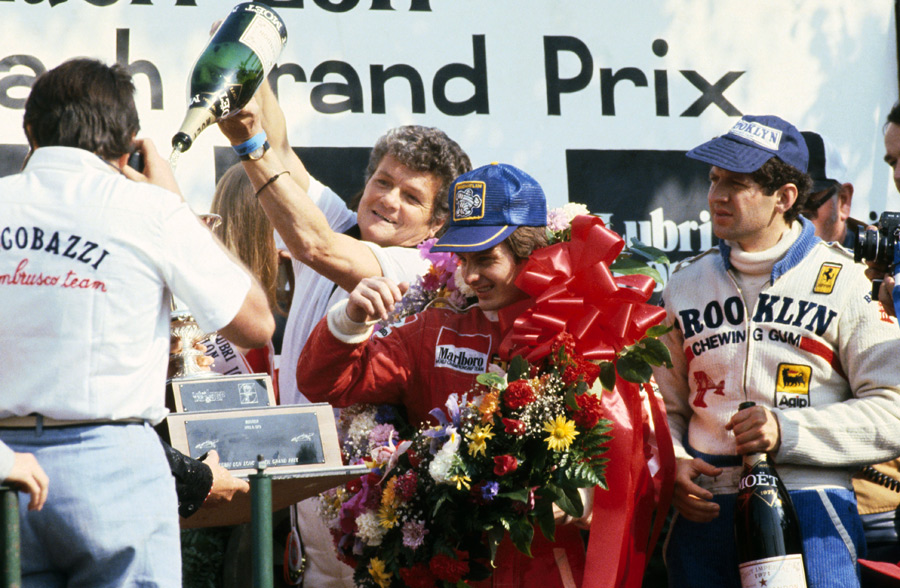 Gilles Villeneuve vcelebrates his win on the podium with second placed team mate Jody Scheckter