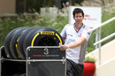 A McLaren mechanic moves tyres through the paddock
