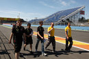 Romain Grosjean walks the track with his Lotus mechanics