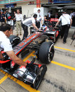 Jenson Button's McLaren is pushed back into the pits