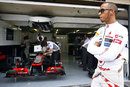 Lewis Hamilton watches on from the front of the McLaren garage