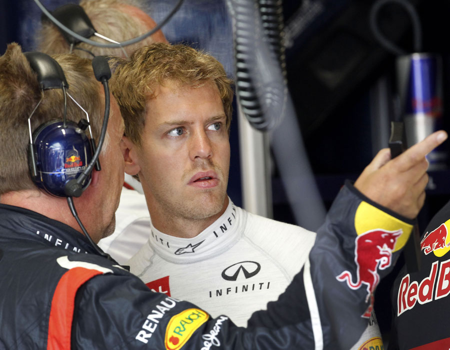 Sebastian Vettel talks to an engineer in the Red Bull garage